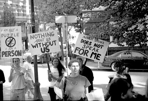 "people holding ""nothing about us without us"" placards"