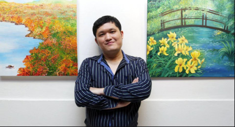 Dennis Liew between two of his paintings hung on a wall