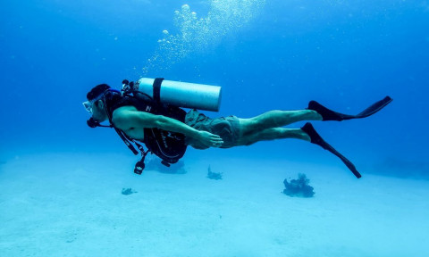 scuba diver swimming in very clear water
