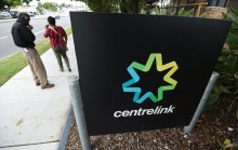 two people smoking near a Centrelink sign