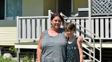 Single mother Anne Heel and her son Christopher in front of their Queensland house