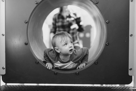 young boy in playground pipe